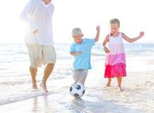 Fader och hans ungar som spelar fotboll tillsammans Arkivfoto