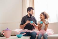 Fader och ledotter som har tebjudningen hemma Arkivfoton