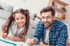 Fader och liten dotter hemma som ligger på golvet som rymmer blyertspennor som ser lycklig närbild för kamera royaltyfri bild