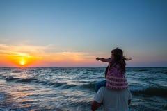 Fader och liten dotter på stranden på solnedgången Arkivbild