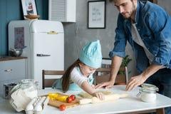 Fader och liten dotter som bakar bakelser Familj som har gyckel i kök och får klar för ett parti royaltyfri bild