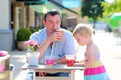 Fader och liten dotter som dricker i kafé Arkivfoton