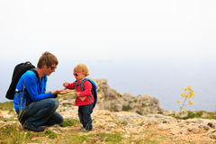 Fader och liten dotter som fotvandrar i berg Fotografering för Bildbyråer