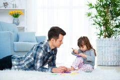 Fader och liten dotter som har kvalitets- familjtid tillsammans hemma farsa med flickan som ligger på varm golvteckning med färgr arkivbilder