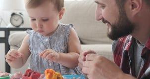Fader och liten dotter som spelar med plasticine lager videofilmer