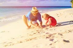 Fader och liten dotter som spelar med sand på stranden Royaltyfri Fotografi
