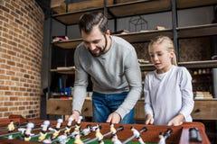 fader och liten dotter som spelar tabellfotboll tillsammans arkivfoto