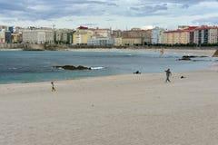 Fader och liten flicka som spelar på den Riazor stranden med en drake La Coruna, Spanien arkivbild