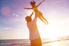 Fader och liten flicka som spelar på stranden Royaltyfria Foton