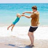 Fader och liten litet barnpojke som har gyckel på stranden Royaltyfri Foto