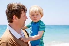 Fader och liten litet barnpojke som har gyckel på stranden Fotografering för Bildbyråer