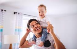 Fader och liten litet barnson inomhus hemma och att spela fotografering för bildbyråer