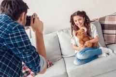 Fader och liten man för dotter som hemma tar foto av dottern med den lyckliga nallebjörnen royaltyfri bild