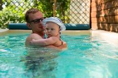 Fader och liten son i en simning för Panama hatt i pölen Royaltyfri Foto