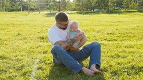 Fader och liten son på gräset i parkera stock video