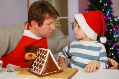 Fader och liten son som förbereder ett pepparkakakakahus Arkivfoton