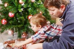 Fader och liten son som hemma dekorerar julträdet Arkivbild