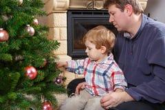 Fader och liten son som hemma dekorerar julträdet Royaltyfria Bilder