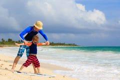Fader och liten son som lär att surfa på Arkivbild