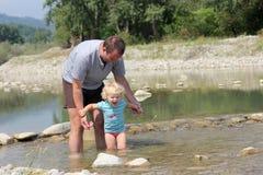 Fader och litet barn som spelar i floden Fotografering för Bildbyråer