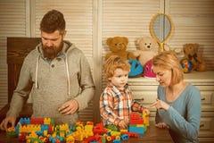 fader och moder med konstruktörn för barnlek pyslek med föräldrar hemma lycklig barndom Omsorg och royaltyfri fotografi