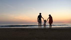 Fader och moder som svänger barnet på stranden lager videofilmer