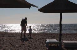 Fader och pojke som spelar på stranden på solnedgångtiden, begrepp av den vänliga familjen royaltyfri foto
