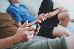 Fader och söner som sitter på en soffa i vardagsrum och spelar videospel Begrepp för avslappnande tid för familj hemmastatt Arkivbilder