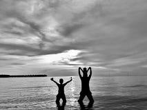 Fader och söner som vänder mot solnedgång Fotografering för Bildbyråer
