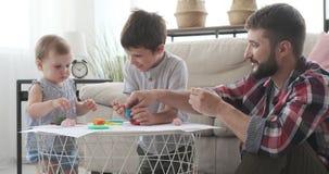 Fader och små barn som spelar med plasticine arkivfilmer