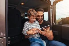 Fader och son baktill av bilen genom att använda den digitala minnestavlan Arkivbild