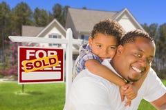 Fader och son för blandat lopp framme av det Real Estate tecknet och huset Arkivbilder