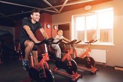 Fader och son i idrottshallen En man och en son är förlovade i motionscykeler tillsammans Royaltyfri Bild