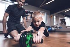Fader och son i idrottshallen Fadern och sonen spenderar tid tillsammans och leder en sund livsstil royaltyfri fotografi