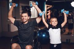 Fader och son i idrottshallen Fadern och sonen spenderar tid tillsammans och leder en sund livsstil arkivbilder