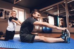 Fader och son i idrottshallen Fadern och sonen spenderar tid tillsammans och leder en sund livsstil royaltyfri foto