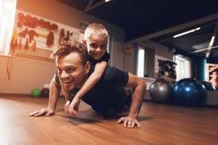 Fader och son i idrottshallen Fadern och sonen spenderar tid tillsammans och leder en sund livsstil arkivfoto