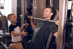 Fader och son i idrottshallen Fadern och sonen spenderar tid tillsammans och leder en sund livsstil royaltyfri bild