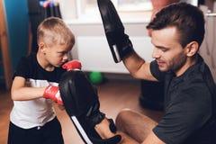 Fader och son i idrottshallen Fadern och sonen spenderar tid tillsammans och leder en sund livsstil royaltyfria bilder