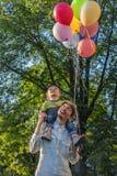 Fader och son i parkera med ballonger Arkivbild