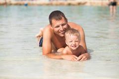 Fader och son i vattnet Royaltyfri Foto