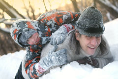 Fader och son i vintern på en kall rulle och lek i snön arkivbilder