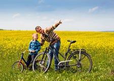 Fader och son med cyklar på landsfält med blommor i soligt Fotografering för Bildbyråer