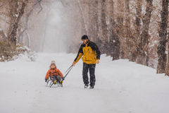 Fader och son med en pulka som är utomhus- i snön Arkivfoton