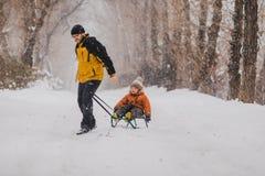 Fader och son med en pulka som är utomhus- i snön Royaltyfri Fotografi