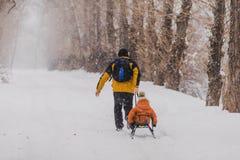 Fader och son med en pulka som är utomhus- i snön Arkivbild