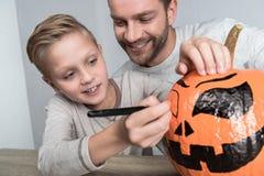 Fader och son med halloween pumpa Arkivfoto