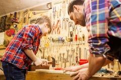 Fader och son med hammaren som arbetar på seminariet arkivbild