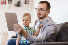 Fader och son med minnestavlaPC:n som hemma spelar Royaltyfria Bilder