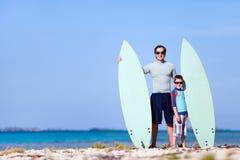 Fader och son med surfingbrädor Arkivbilder